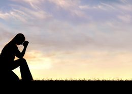 A silhouette of a young Christian woman is bowing her head in prayer, and desperation outside during sunset.