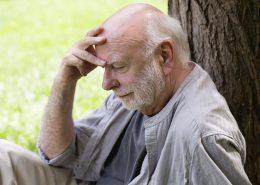homme songeur assis contre un arbre dans un parc